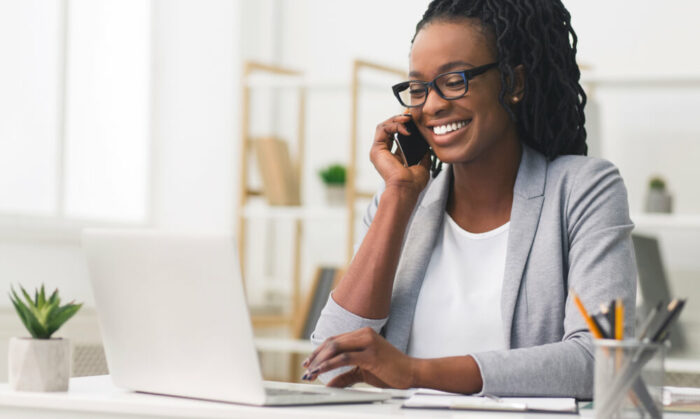 woman looking at laptop while talking on phone