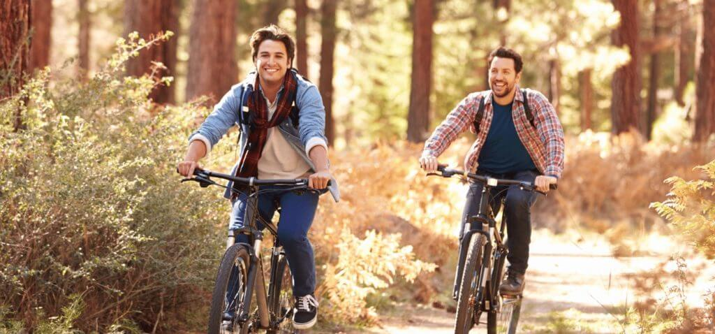 Two younger men riding bikes in the forest