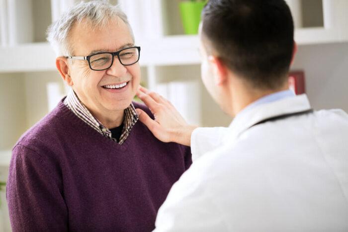 senior man being reassured by doctor